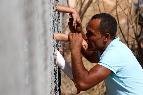 Syrian family shares kisses through fence