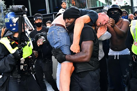 Black man carries suspected far-right protester to safety