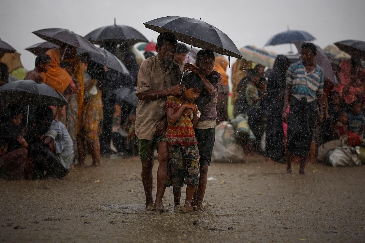 Rohingya refugees try to take shelter from torrential rain as they are held by the Border Guard Bangladesh (BGB) after illegally crossing the border, in Teknaf.
