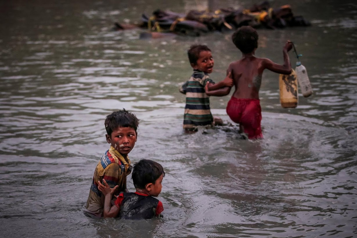 Rohingya siblings fleeing violence hold one another as they cross the Naf River along the Bangladesh-Myanmar border in Palong Khali, near Cox's Bazar.