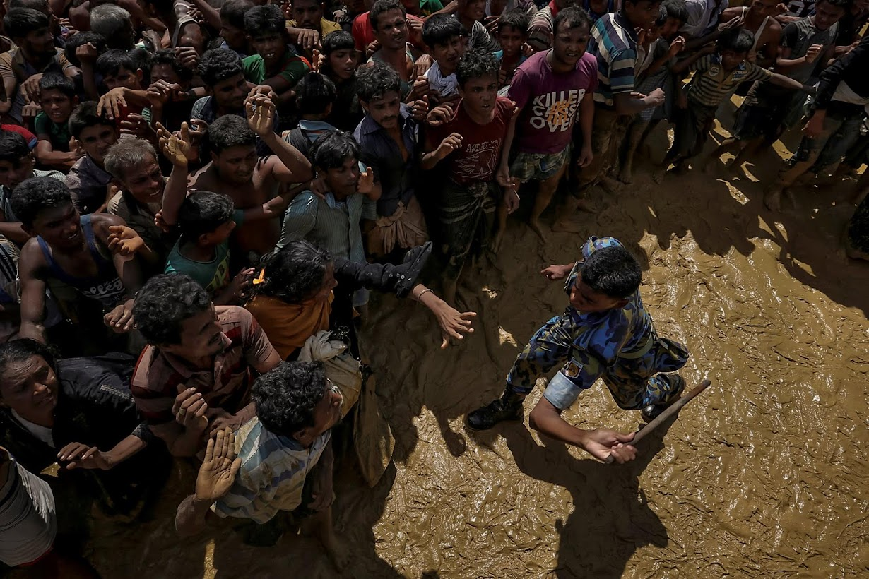 A security officer attempts to control Rohingya refugees waiting to receive aid in Cox's Bazar.