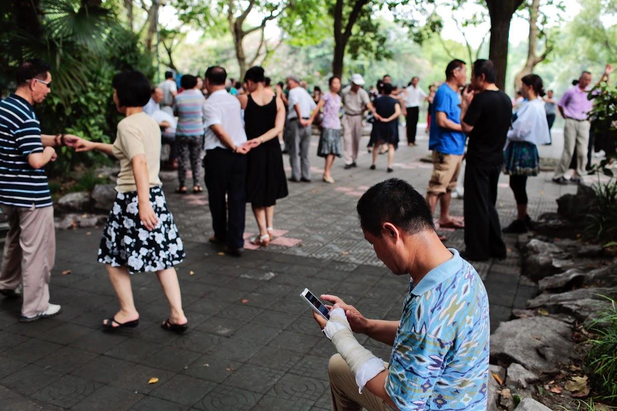 自宅近くの公園で、ダンスの合間に携帯で株価をチェックする電気技師のGao Haibaoさん(55)