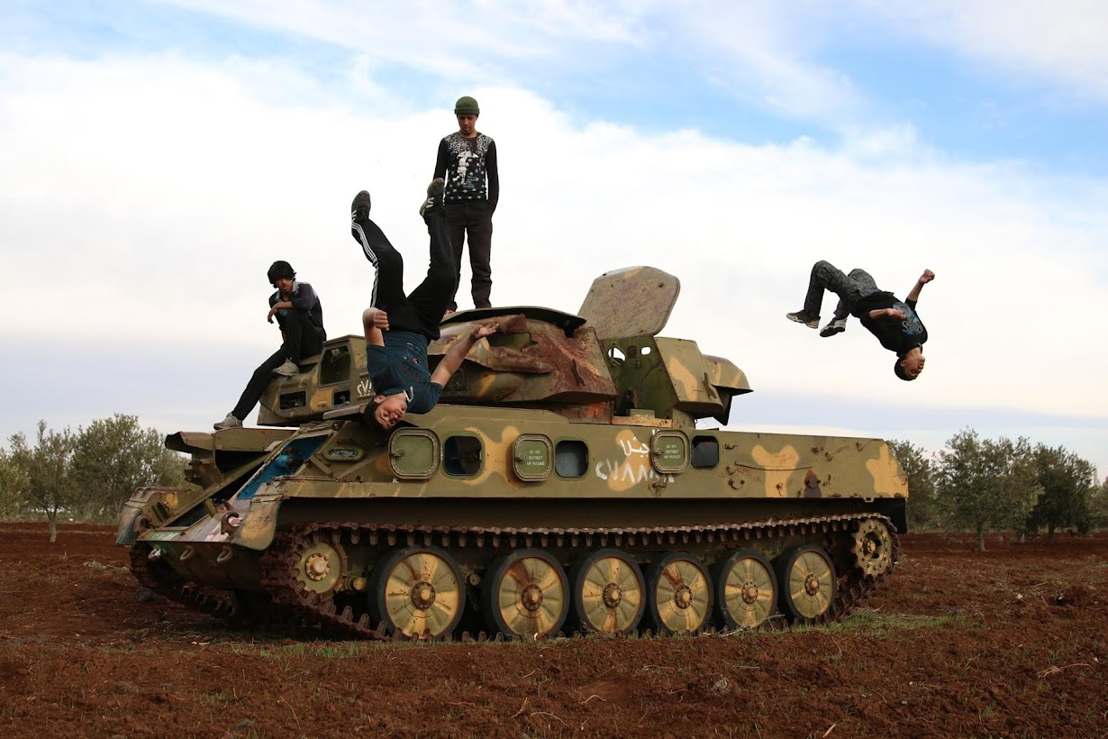 軍事車両を使ってパルクールを練習するムハンナド・アルカディリ君(右)ら。シリア南部インヒルで撮影(2017年 ロイター/Alaa Al-Faqir)