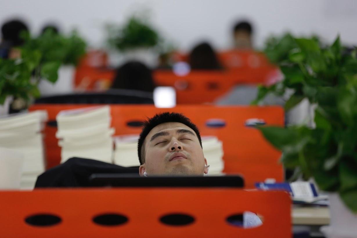 昼食後、自分の席で昼寝をするCui Mengさん。北京で4月撮影(2016年 ロイター/Jason Lee)