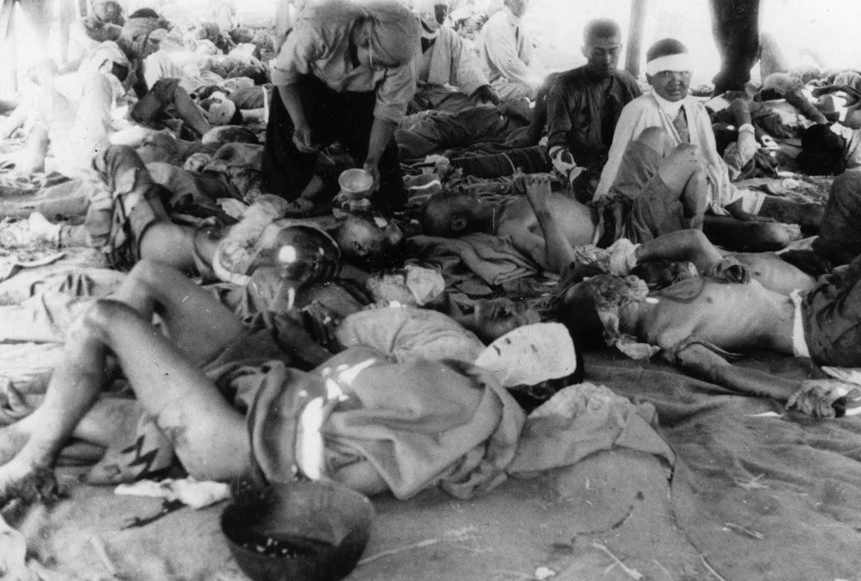 原爆投下後、広島・太田川の土手に設けられた救助施設で、手当てを受ける被爆者。1945年8月9日撮影(2016年 ロイター/広島平    和記念資料館提供)