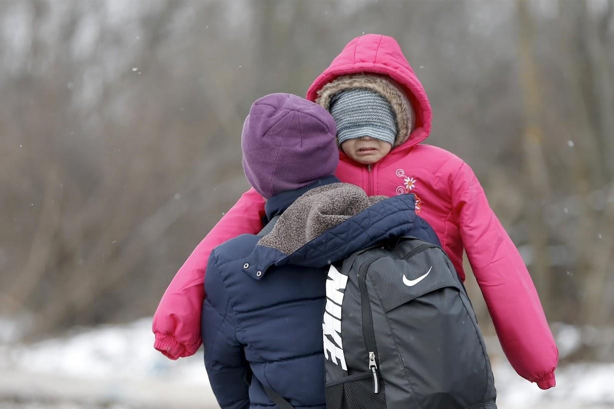 子供を抱きかかえながら、セルビアの村を歩く難民。
