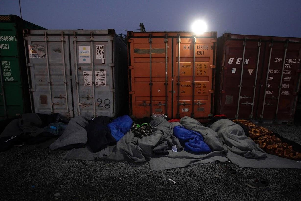 ギリシャとマケドニアの国境を渡る許可を待つ間、コンテナのそばで眠りにつく難民や移民たち