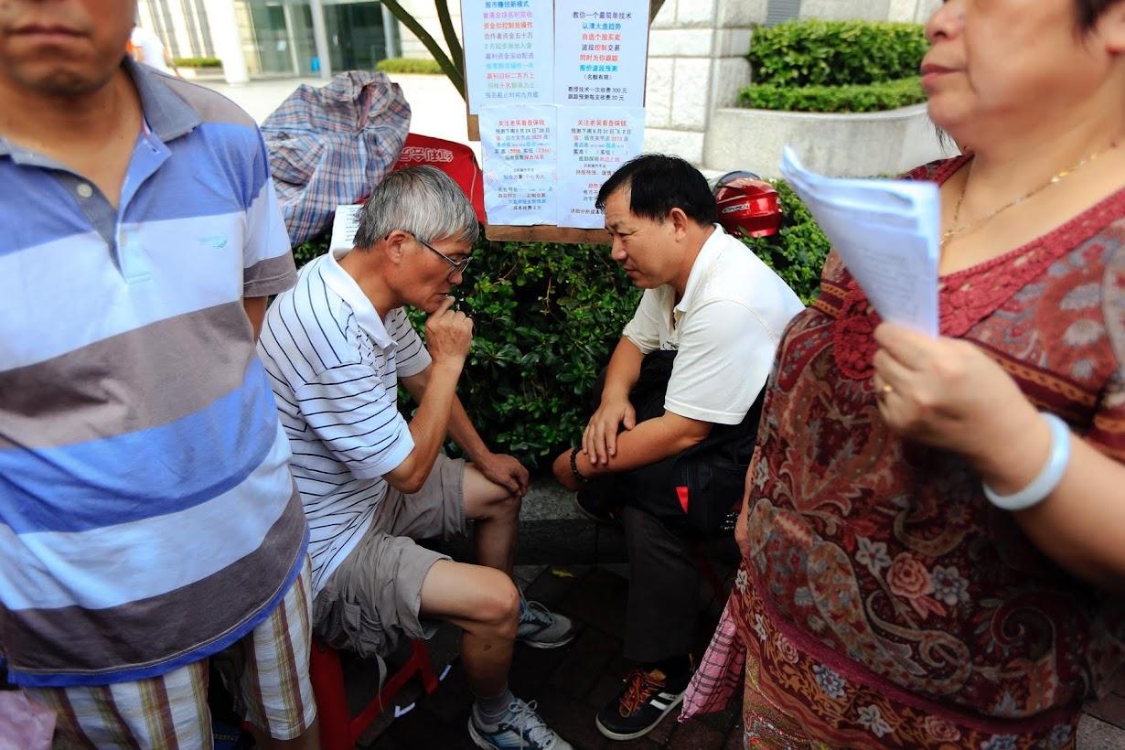 上海の「路上株式サロン」で投資アドバイスをするWu Lin'anさん(写真左奥)