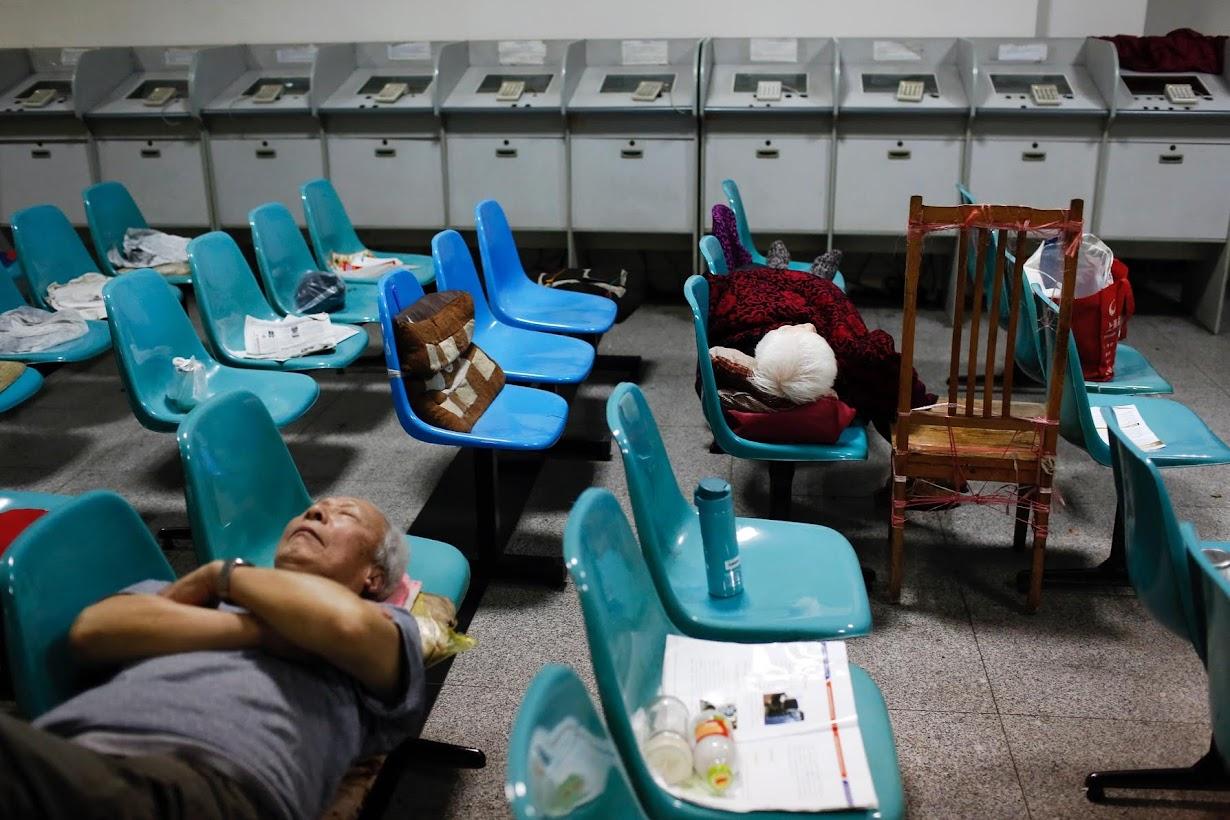 上海の証券会社で昼寝する人々