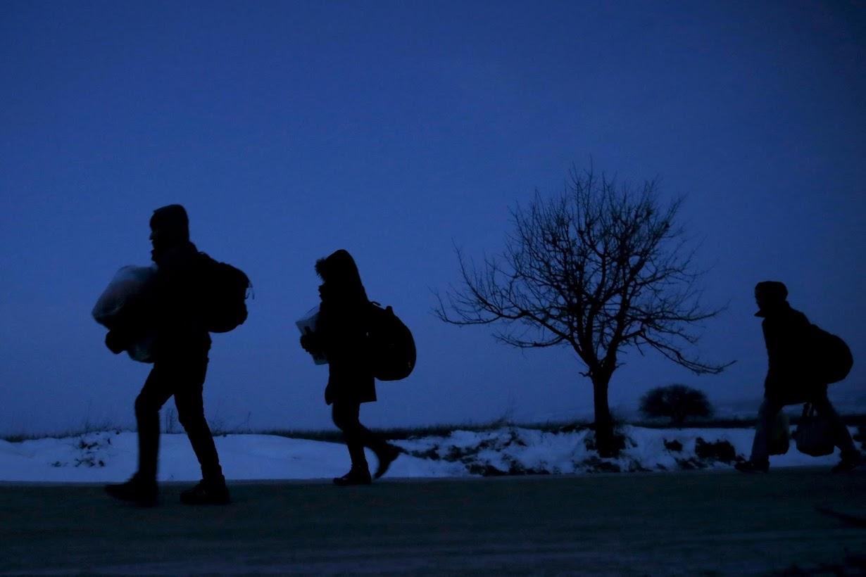 マケドニアから国境を越え、セルビアの村を歩く難民たち。